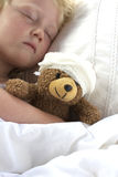 Girl in bed cuddling a teddy with bandage Stock Image