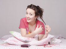 Girl in bed cutting lock of hair cuticle scissors Stock Photos