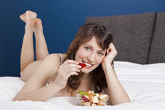 Girl on bed eating fruits Royalty Free Stock Photo