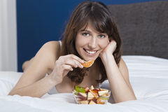 Girl on bed eating fruits Stock Photo