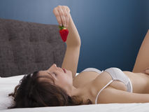 Girl on bed eating strawberries Stock Images