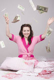 The girl on bed falling banknotes Stock Photography