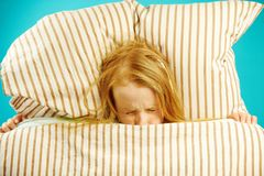 Girl in bed with fear closed her eyes, concerned, sees nightmares, afraid to get out from under blanket, top view. royalty free stock images