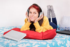 Girl in bed with headphones, book and a laptop Stock Photo