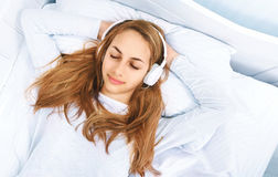 Girl in bed with a headphones on listening to the music. Stock Photos