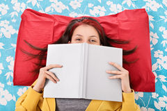 Girl in bed hiding her face behind a book Stock Photography