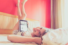 Girl on bed with ipad. Laughing blonde teenage girl with her head on the pillow and her legs and feet resting on a wall painted red. A stylish ipad rests on her Stock Image
