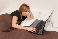 Girl in Bed with Laptop. Young pretty girl working on a laptop at home in bed stock image