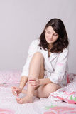 Girl in bed paints her toenails Royalty Free Stock Photo