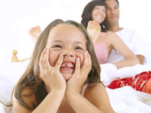 Girl in bed with parents, smiling, close-up, cut out Royalty Free Stock Image
