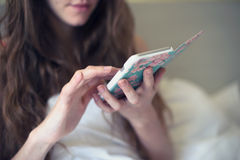 Girl in bed with the phone communicates in the internet Royalty Free Stock Images