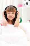 Girl on bed. Playful pretty little girl with headphones, relaxing on a bed, indoors Royalty Free Stock Photos