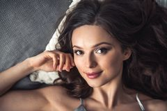 Girl in bed. Portrait of beautiful young girl looking at camera and smiling while lying in bed at home Stock Photos