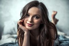 Girl in bed. Portrait of beautiful young girl looking at camera and smiling while resting in bed at home Stock Photos