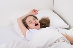 Girl in bed pulling her arms to wake up stock photos