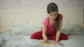 Girl on a bed reading a book stock video footage