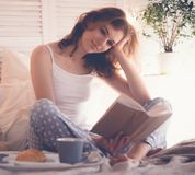 Girl in bed reading and drinking coffee. Lifestyle and people concept:Girl in bed reading and drinking coffee stock photo