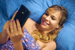 Girl In Bed Reading Love Phone Message From Boyfriend Stock Photography