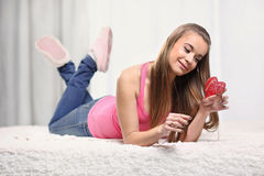 Girl on the bed with red heart. Girl is lying on the bed with red heart Stock Images