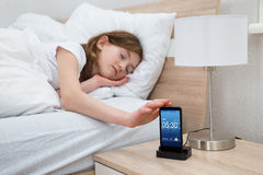 Girl On Bed Snoozing Mobile Phone Alarm Stock Images