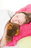 Girl in bed with stuffed bear royalty free stock image