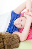 Girl in bed with stuffed bear Stock Image