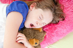Girl in bed with stuffed bear Royalty Free Stock Photography