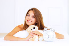 Girl in bed with a teddy bear Stock Photos