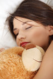 Girl in bed with teddy bear Stock Image