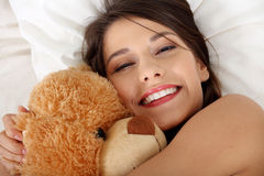 Girl in bed with teddy bear Royalty Free Stock Photography