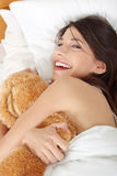 Girl in bed with teddy bear Stock Photography