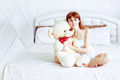 Girl in bed with Teddy bear Royalty Free Stock Photos