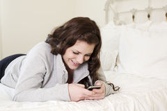Girl on Bed Texting Stock Photos