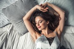 Girl in bed. Top view of beautiful young girl smiling while sleeping in bed at home Royalty Free Stock Photo