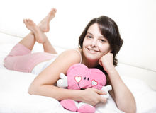 Girl in bed with toy. Young woman lying in bed wearing pajamas holding a pink toy Stock Photos
