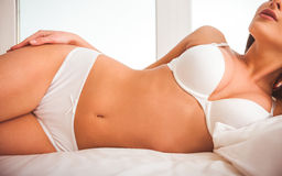Girl on bed in underwear Stock Image