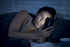 Girl in bed using mobile phone late at night at dark bedroom lying happy and relaxed. Young beautiful womanl in bed using mobile phone late at night at dark stock photography
