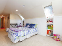 Girl bedroom with attic ceiling and beige carpet with toys. Stock Photos