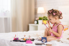 Girl in the bedroom on the bed paints eyes with makeup royalty free stock photo