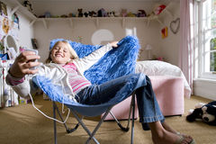 Girl (8-10) in bedroom on blue shag pile chair, listening to MP3 player, smiling stock photo
