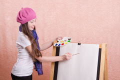 Girl begins to draw picture on the easel Royalty Free Stock Photos