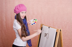 The girl begins to draw picture on the easel Royalty Free Stock Photos