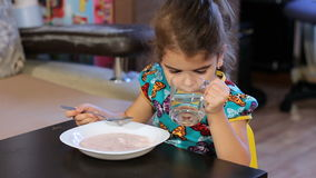 The girl begins to eat porridge. Washed down with a glass of water. stock footage