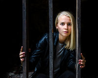 Girl behind bars. A young woman trapped behind bars in a cell Stock Photo