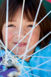 Girl behind a bike wheel. Stock Photo