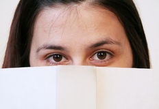 Girl behind book. Girl looking at camera behind book.Copyspace on the book Royalty Free Stock Photography