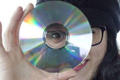 Girl behind a CD. Looking by the hole Stock Photo