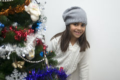 Girl behind Christmas tree Stock Images