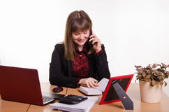 The girl behind the desk office conducts a dialogue by phone Stock Image