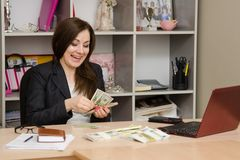 Girl behind desk in office feverishly counts banknotes with a triumphant smile Stock Photos